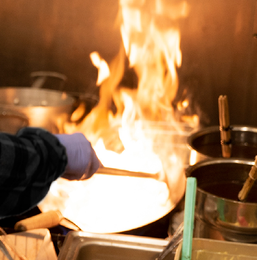 Food being cooked in a Wok over a flame class=